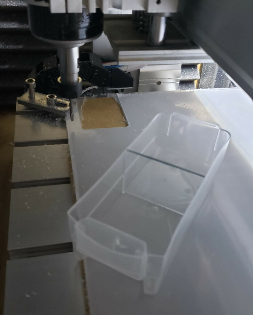 Installed polycarbonate drawer divider, next to the CNC setup it was cut on.